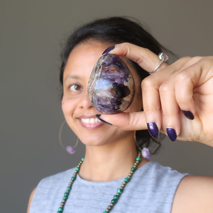 sheila of satin crystals holding up a purple amethyst egg