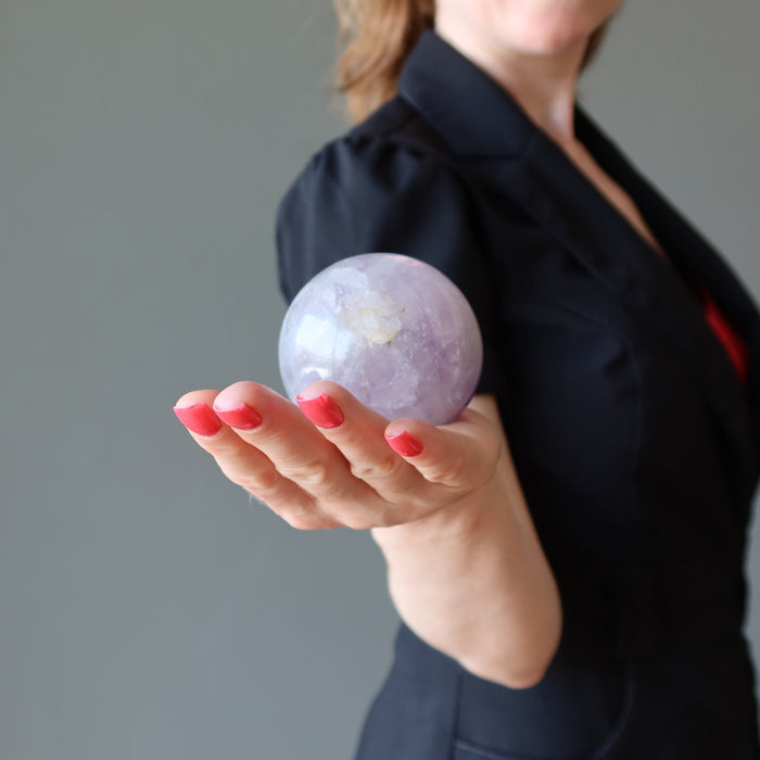 female holding a light purple amethyst sphere