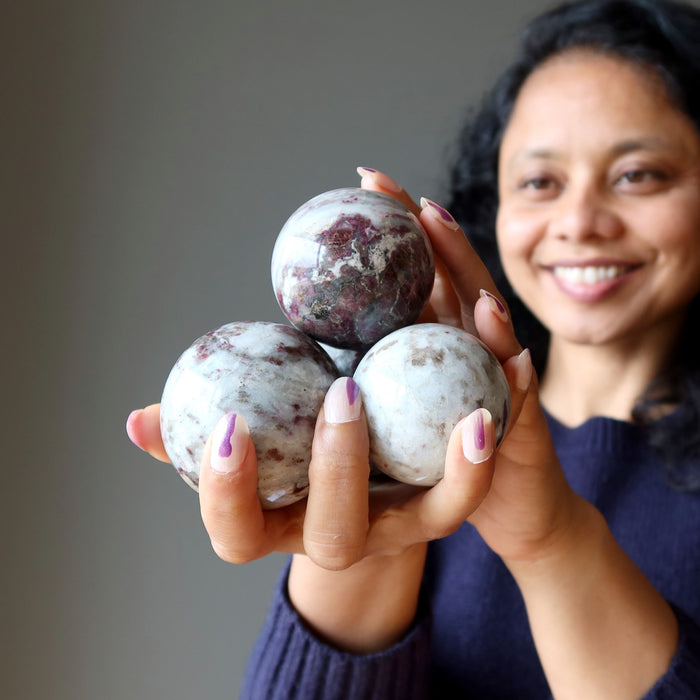 sheila of satin crystals holding up a pile of tourmaline quartz spheres