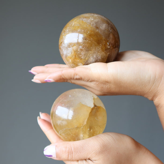 hands holding golden quartz spheres