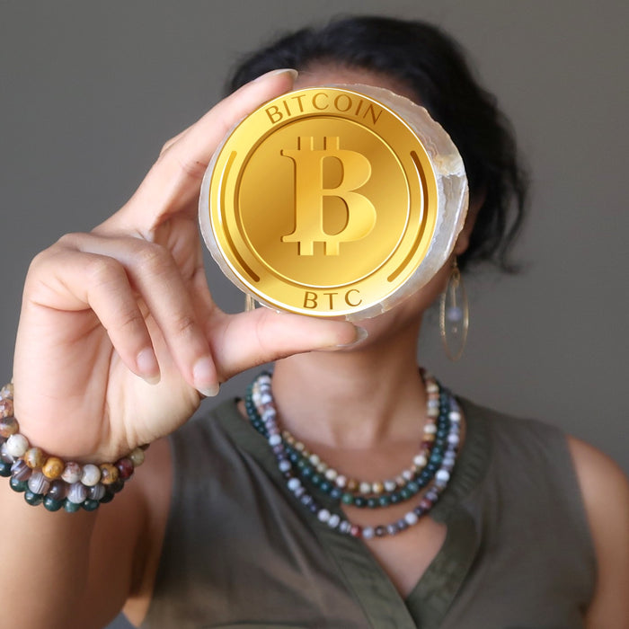 female wearing agate jewelry holding a bitcoin symbol over face