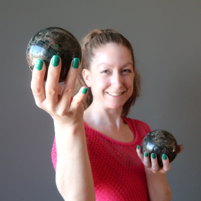 female model holding two chalcocite spheres