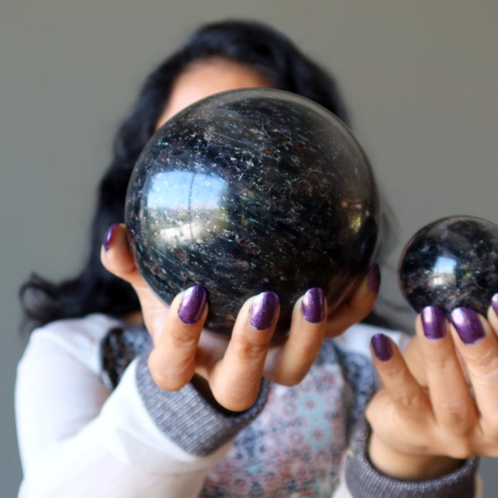 female model holding up two black arfvedsonite spheres