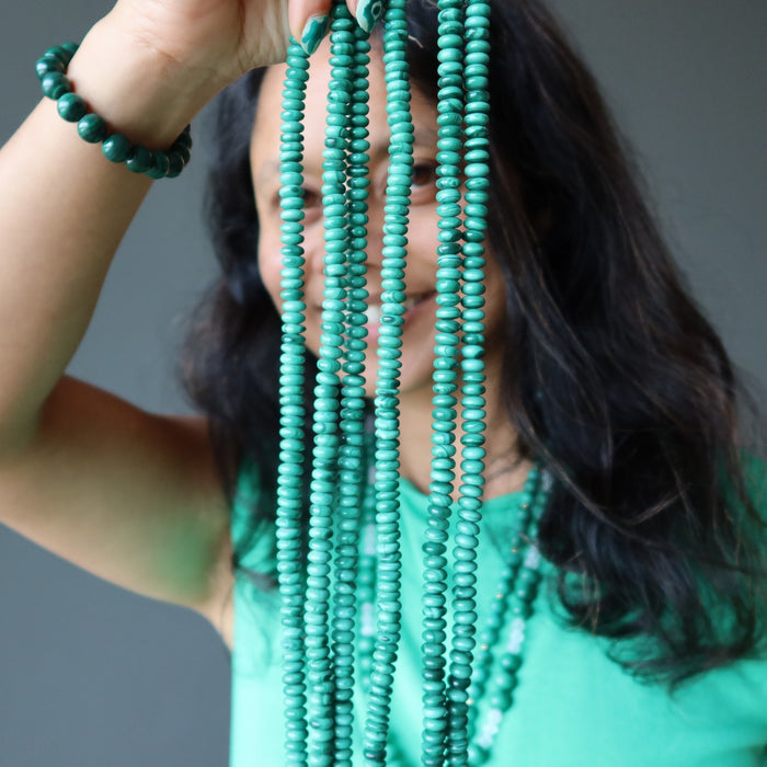sheila of satin crystals holding strands of malachite beads in front of her