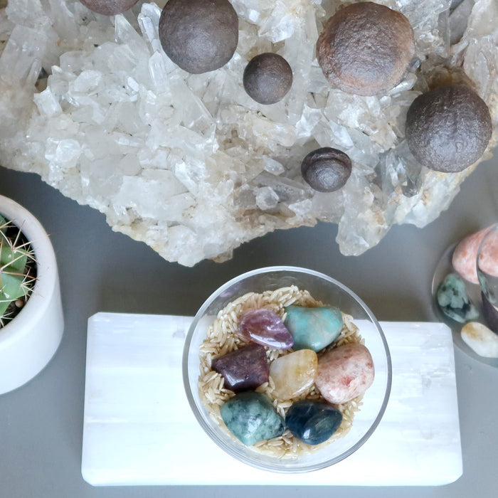 tumbled stones and moqui balls on quartz cluster, selenite slab, in water, in a cactus pot and on brown rice