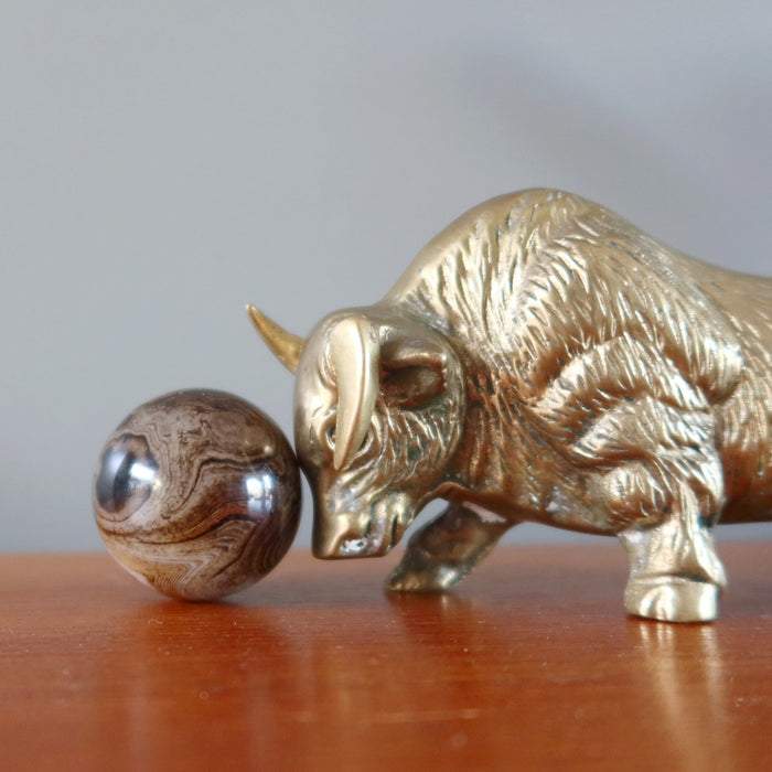 metal bull ox pushing a sardonyx sphere with its head