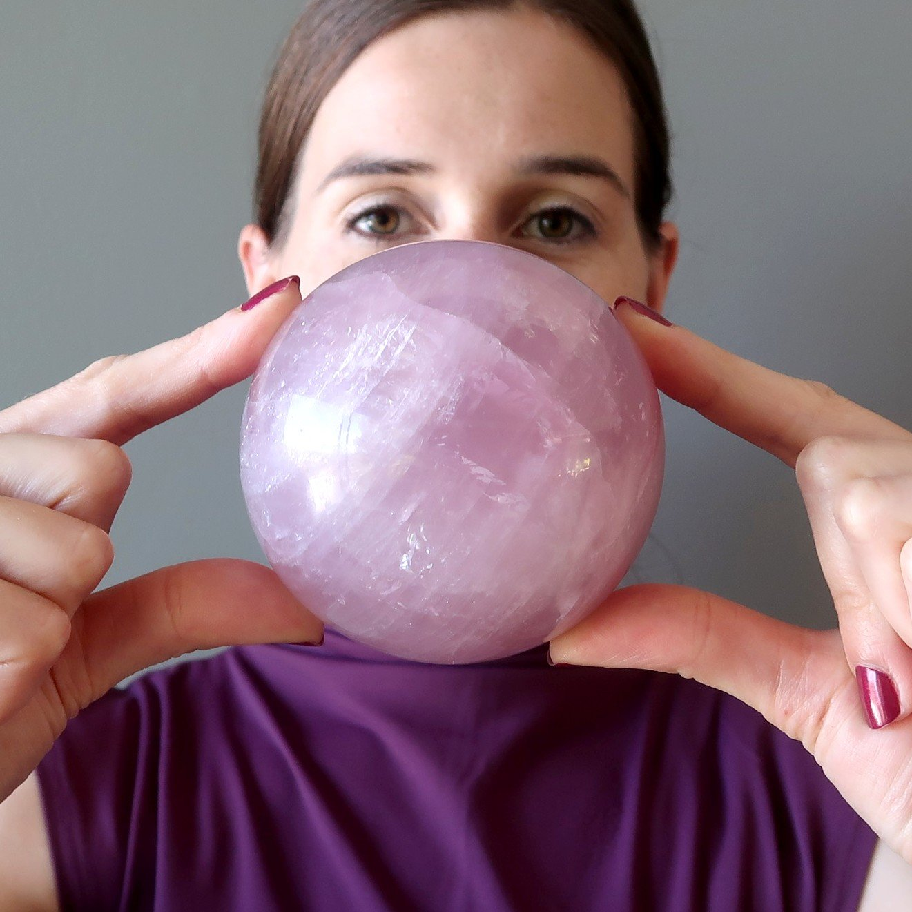 lucia of satin crystals holding up a pink rose quartz crystal ball