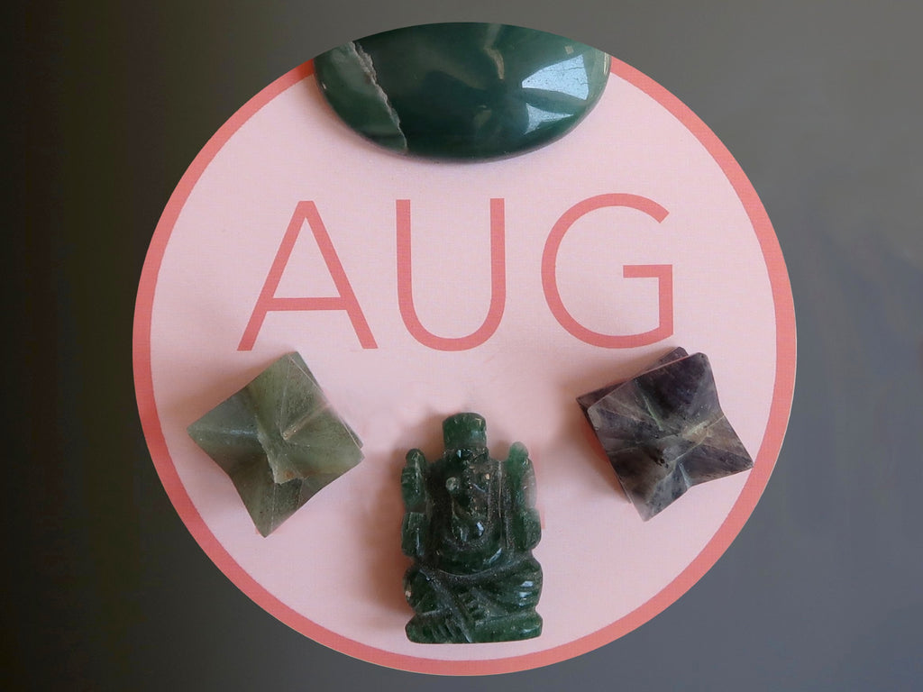 aventurine gemstones on a pink circle inscribed with AUG