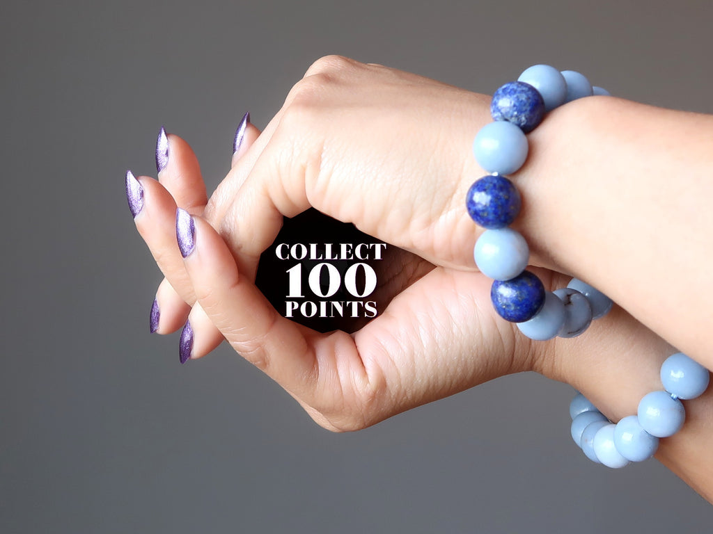 hands wearing blue angelite and lapis bracelets forming a cave with the word collect 100 points written inside