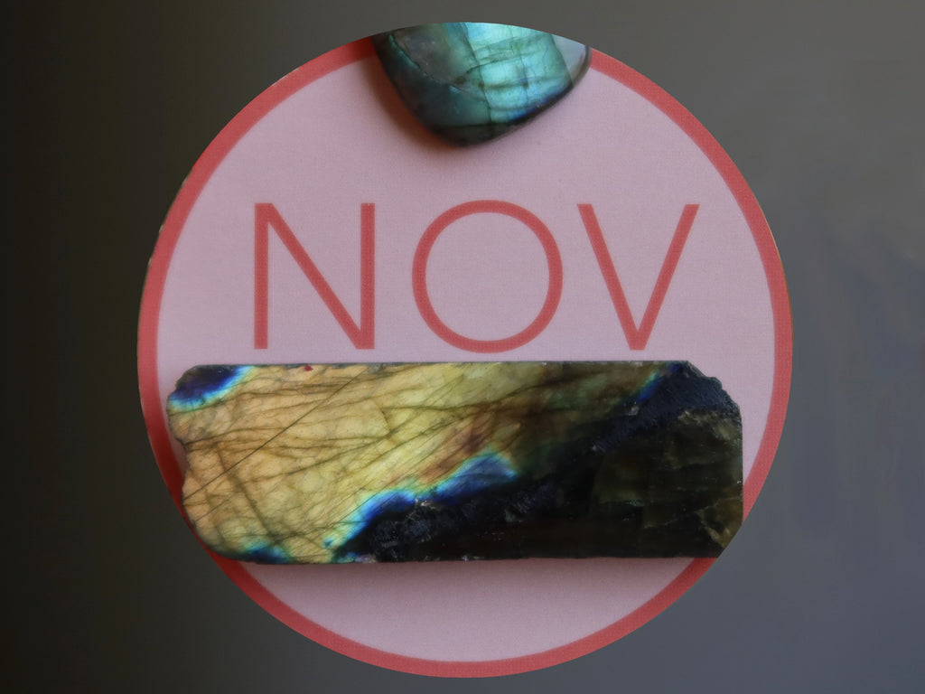 letters NOV in a pink circle with two labradorite stones
