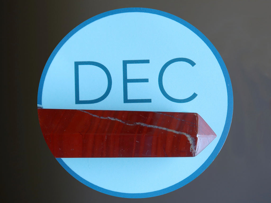 blue circle with letters DEC and a red jasper wand
