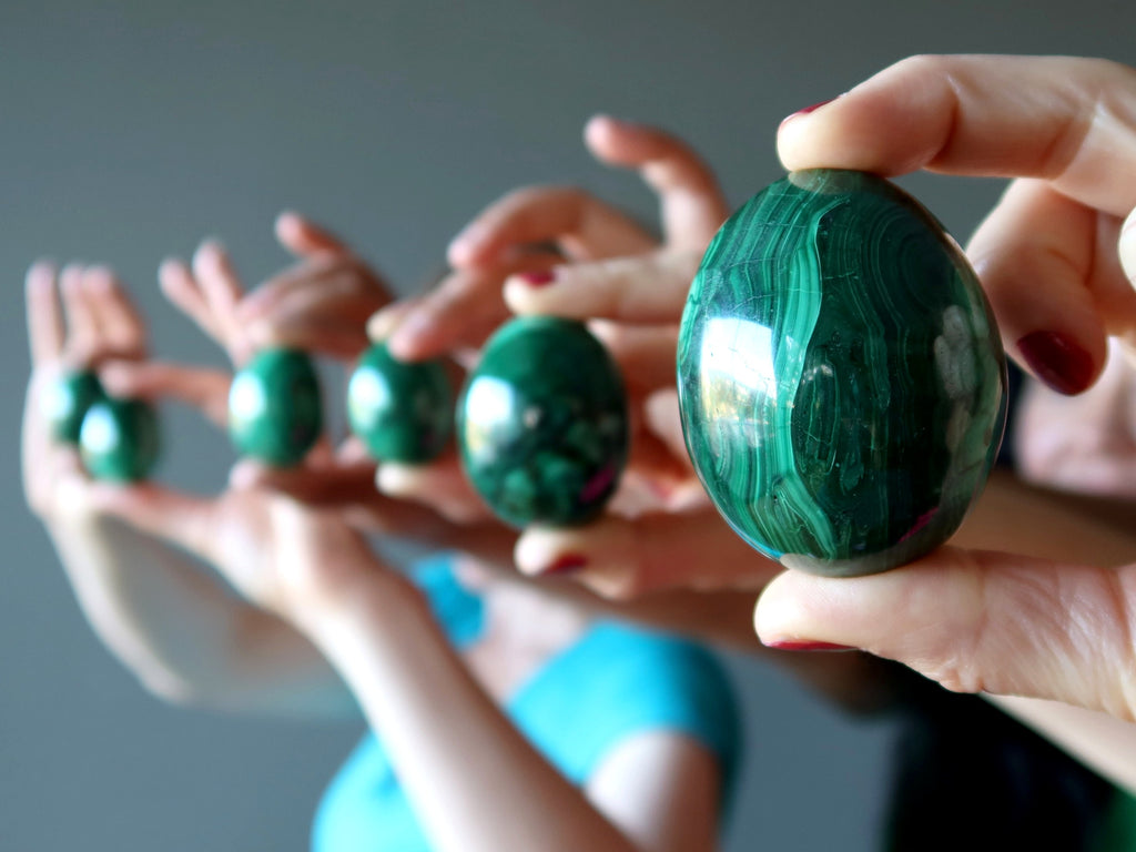 hands holding up a row of green malachite eggs