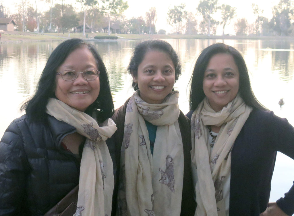 satin mother and daughters posing by a lake
