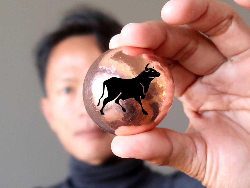 man holding a copper sphere inscribed with a black ox