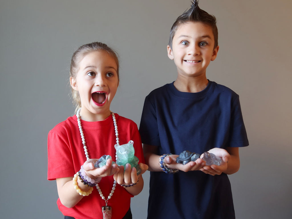 two kids holding crystal animal carvings in their hands