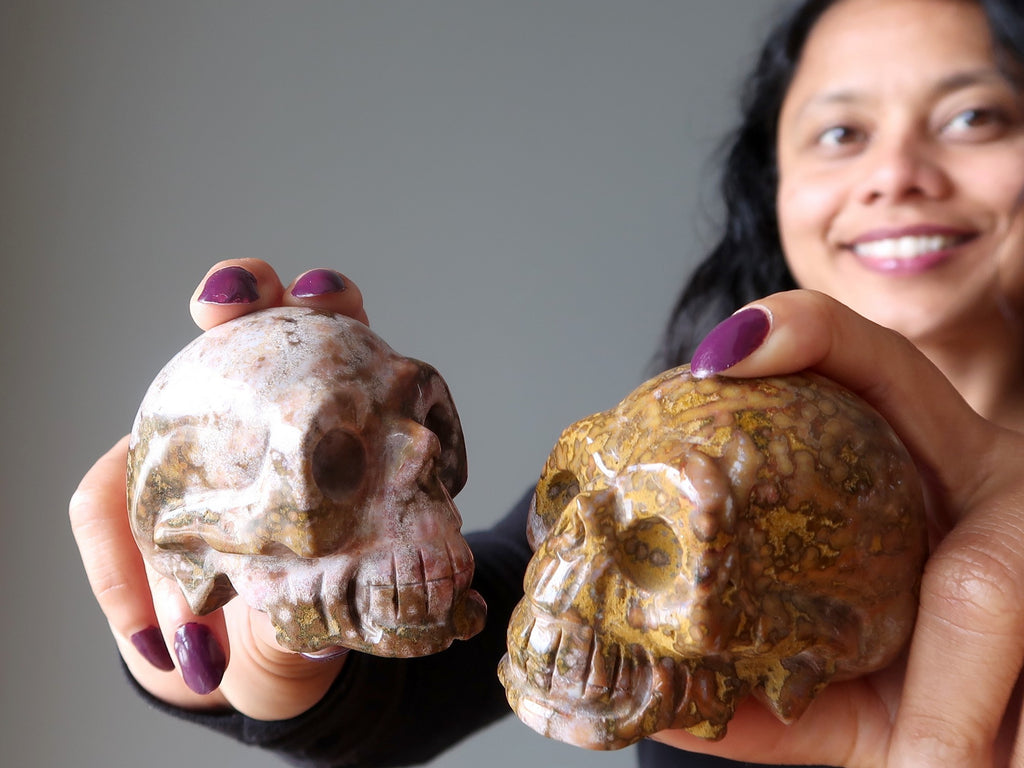 sheila of satin crystals holding up two leopard jasper skulls
