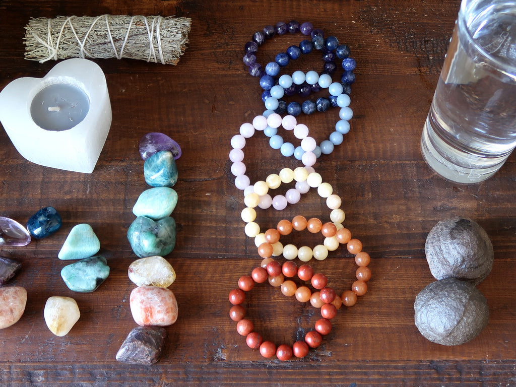 chakra stones, water, moqui marbles, sage and candle for meditation preparation