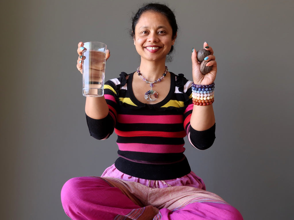sheila of satin crystals holding up water and moqui marbles for post meditation grounding