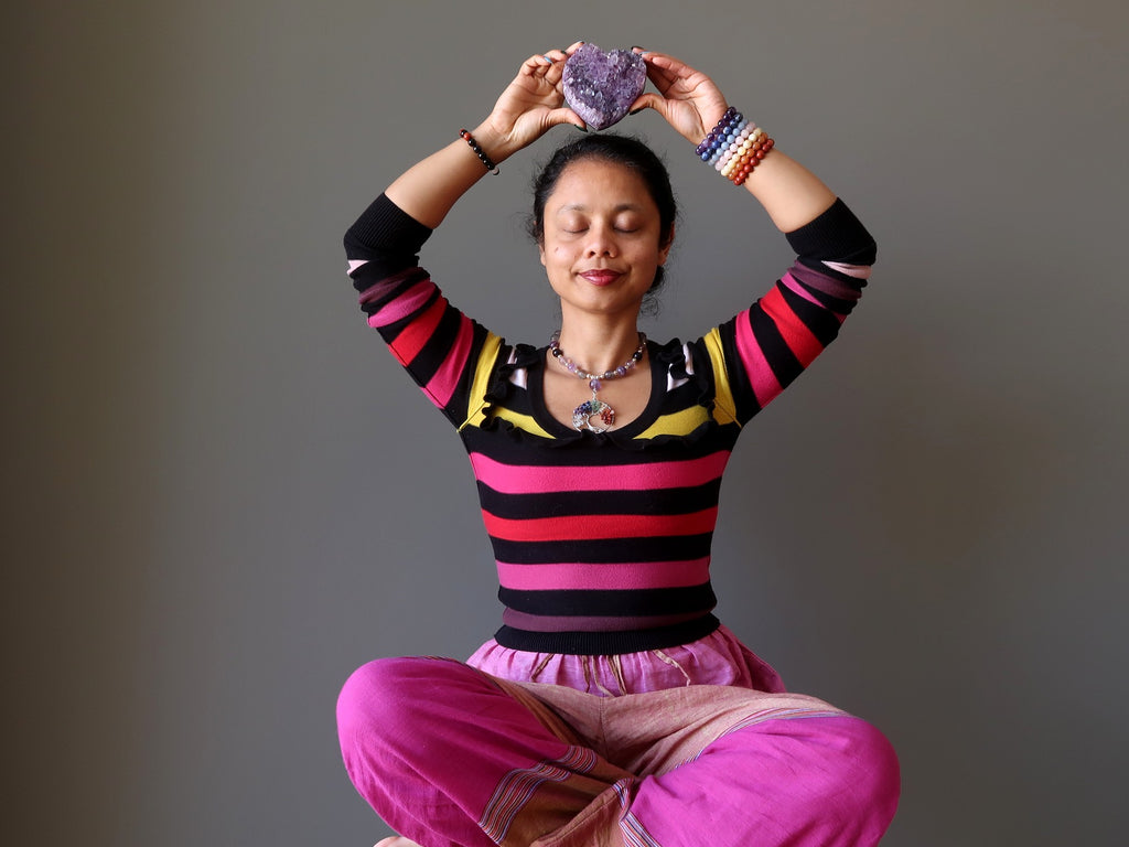 sheila of satin crystals meditating with a amethyst geode heart at her crown chakra