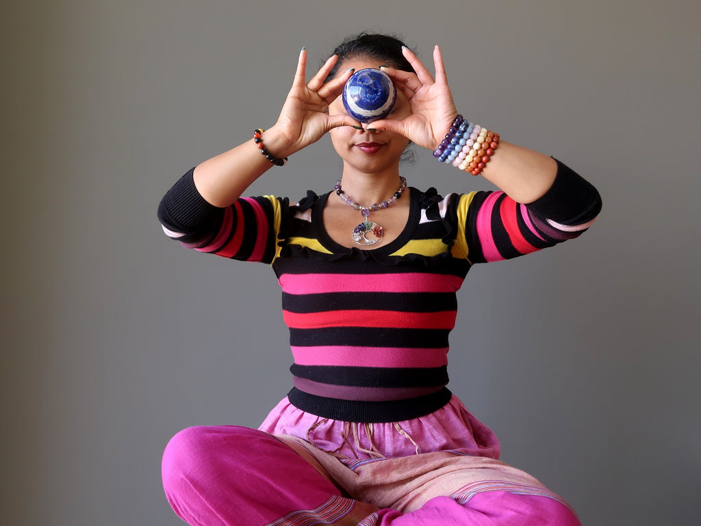 sheila of satin crystals meditating with a lapis lazuli crystal ball at her third eye chakra