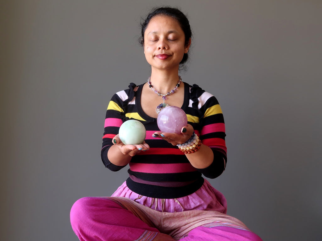 sheila of satin crystals meditating with green jade and pink rose quartz spheres at the heart chakra