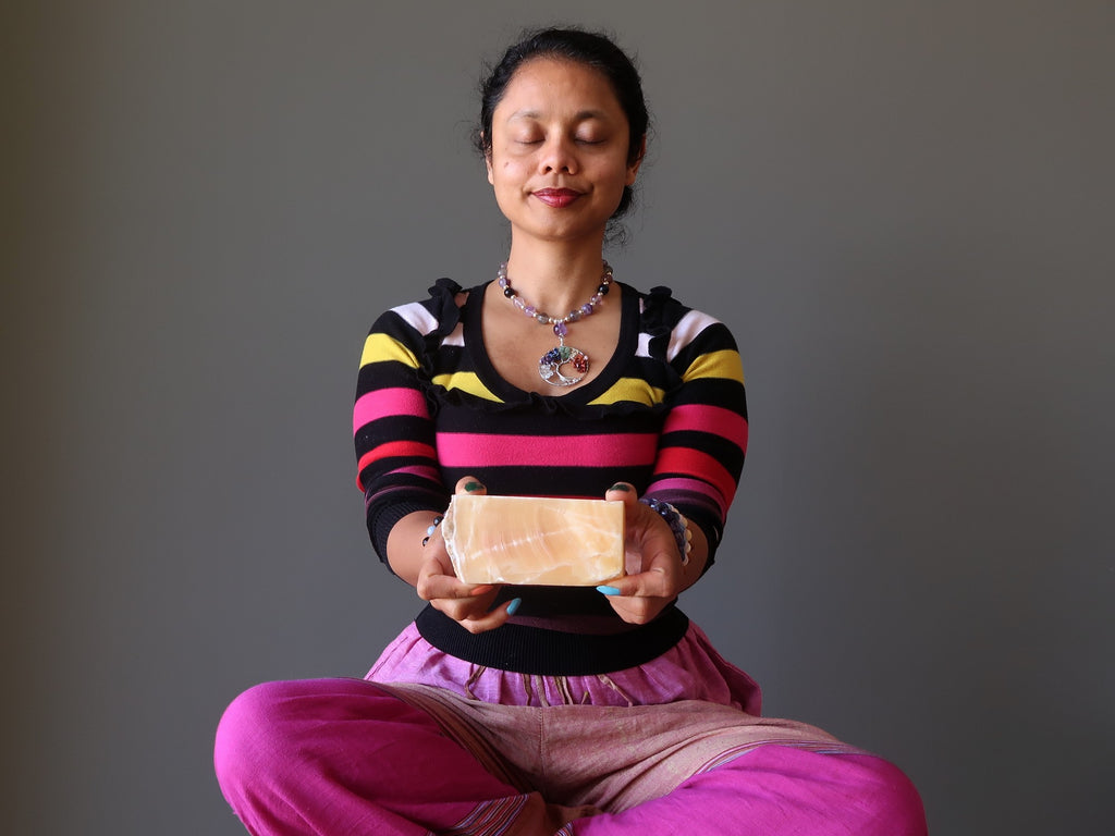 sheila of satin crystals meditating with a yellow calcite block at her solar plexus chakra