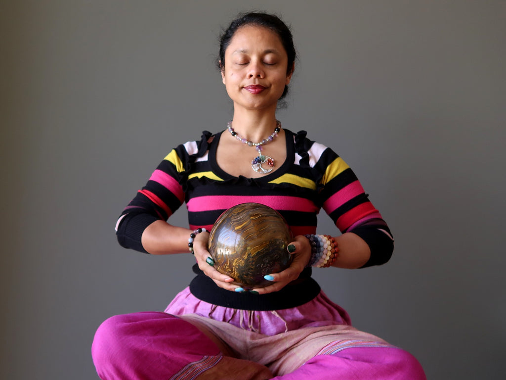 sheila of satin crystals meditating with a large tigers eye sphere