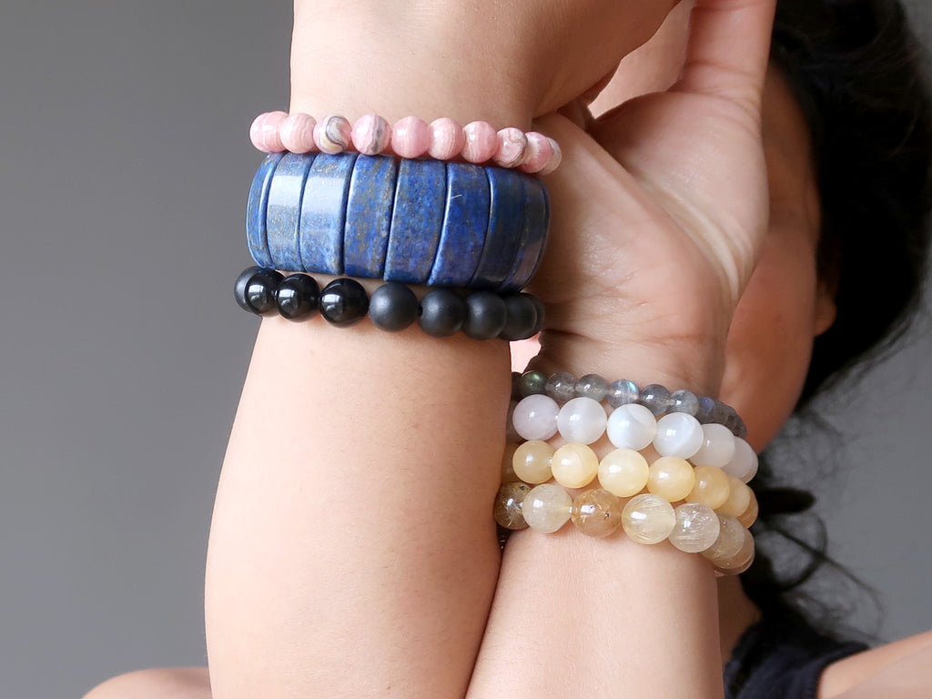 arms stacked with 7 crystal healing bracelets