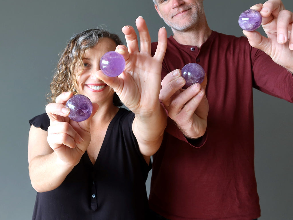 man and woman holding purple amethyst spheres