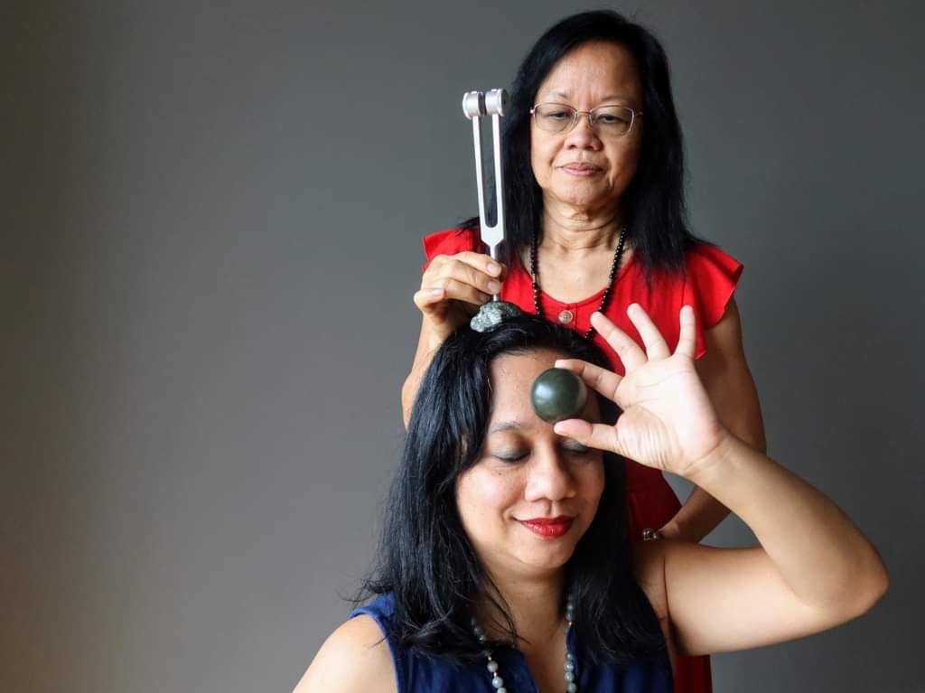 Healer using tuning fork on client with Jade on third Eye chakra