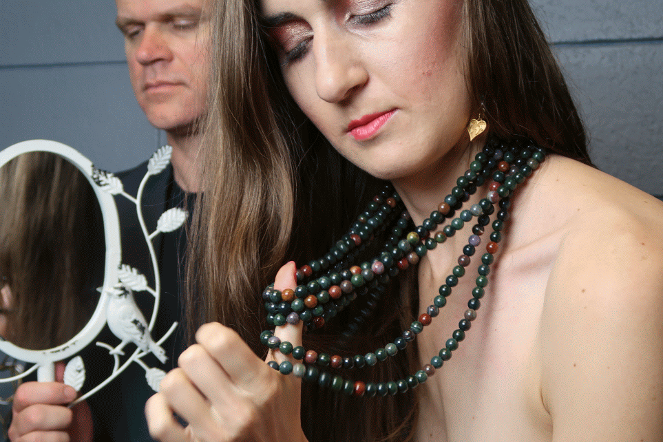 female admiring her layers of bloodstone beaded necklaces as man sits stoically behind her with mirror