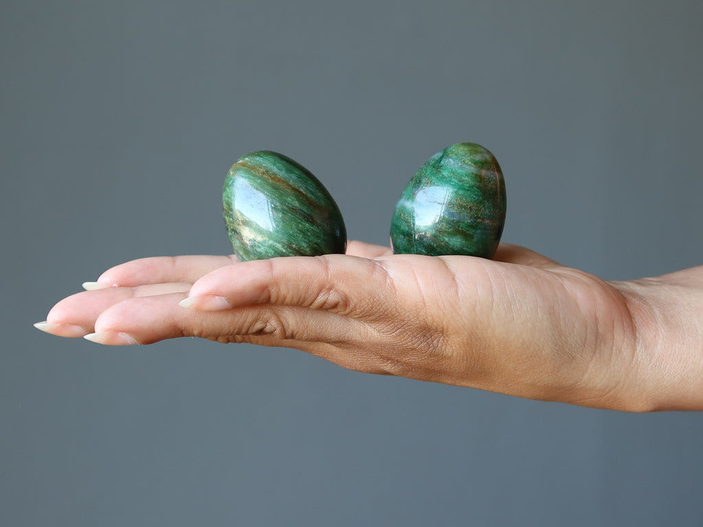 hand holding two green aventurine stone eggs
