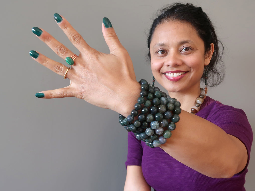 Wearing a stack of green moss agate bracelets