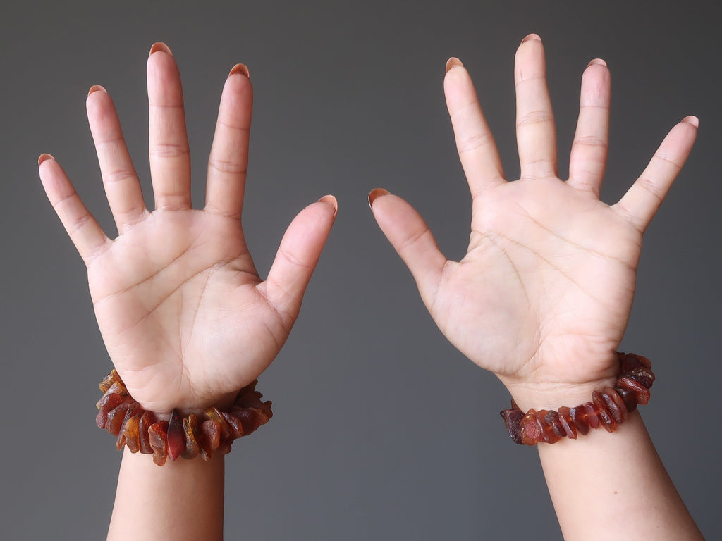 two hands in the air wearing chunky golden orange amber bracelets