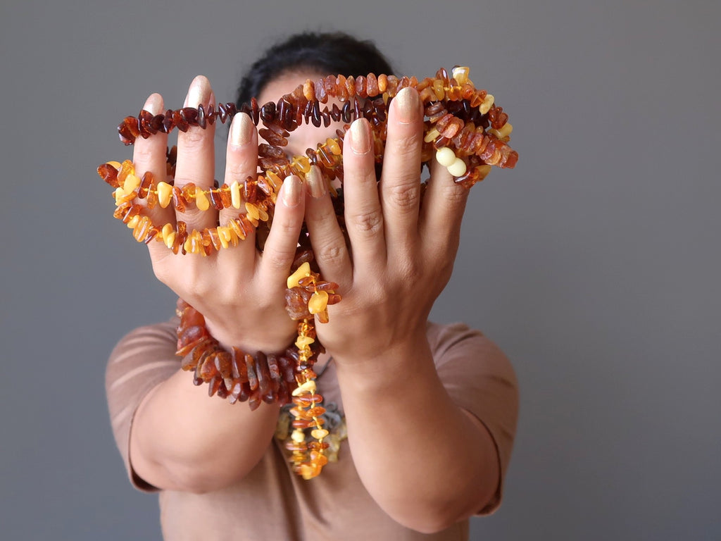 sheila of satin crystals holding up multiple strands of golden baltic amber beaded necklaces