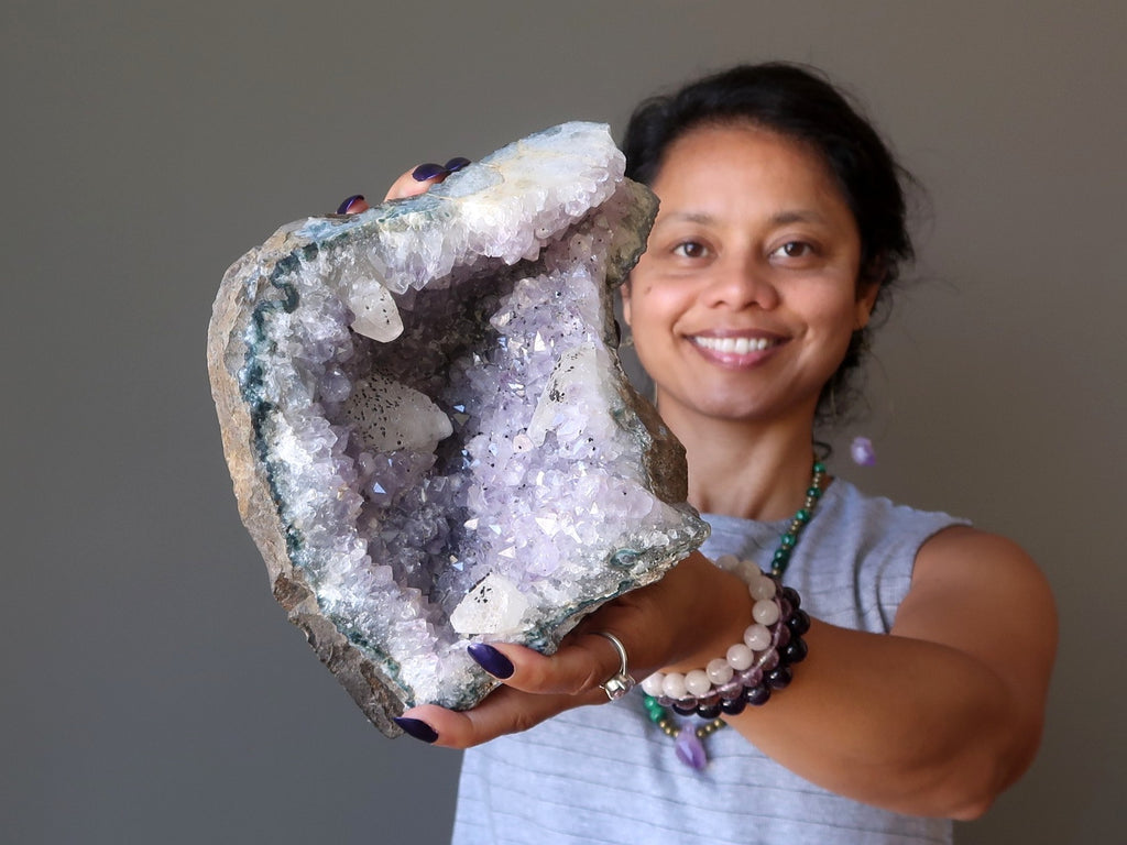 sheila of satin crystals holding up a large amethyst geode