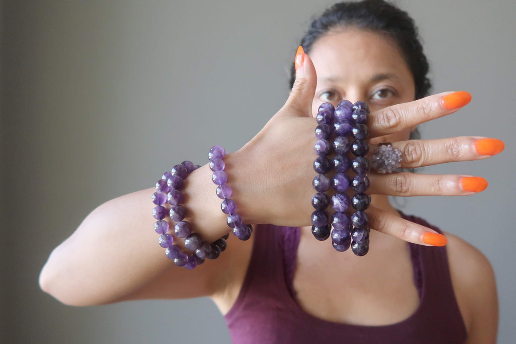 Model with hand full of Amethyst stretch bracelets  and Amethyst cluster ring standing against gray wall.