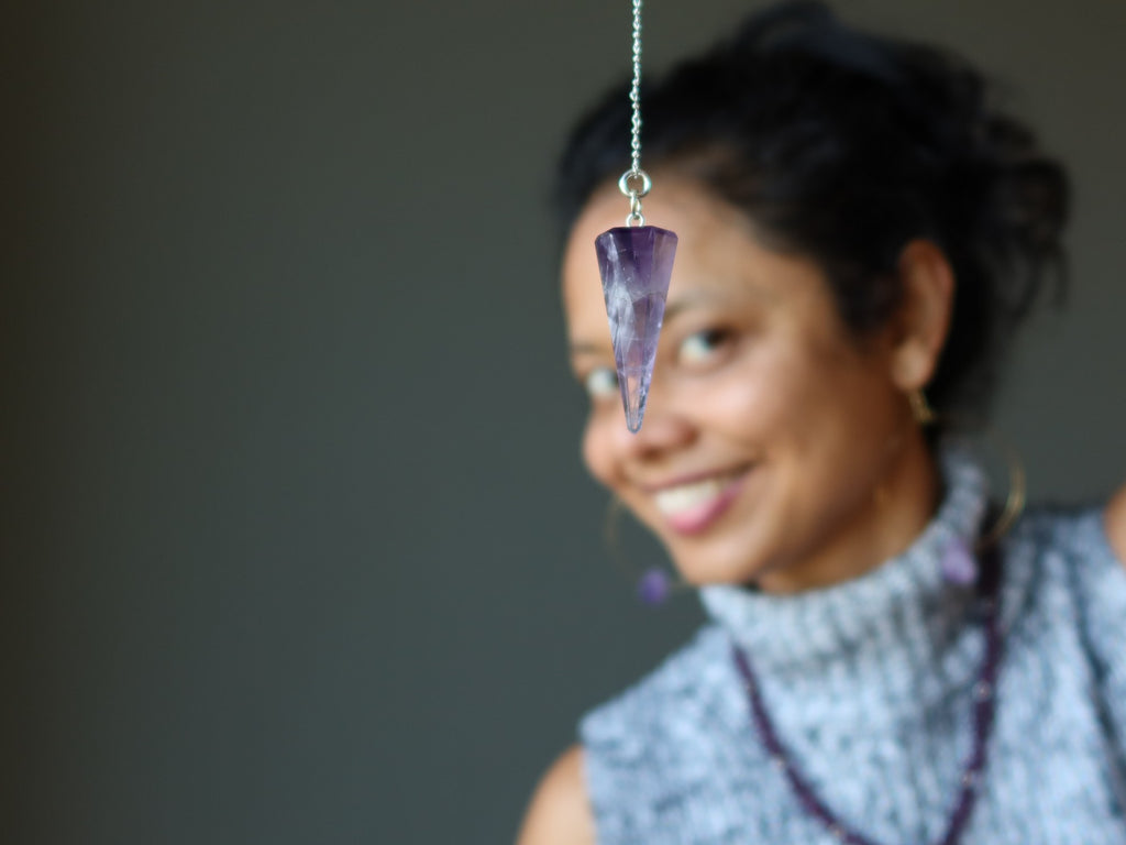 sheila of satin crystals with amethyst pendulum at her third eye chakra