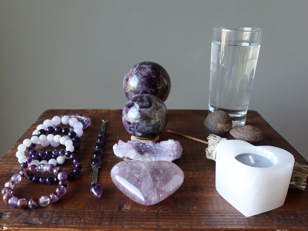 table of amethyst jewelry, stones, water, moqui marbles and candle for meditation