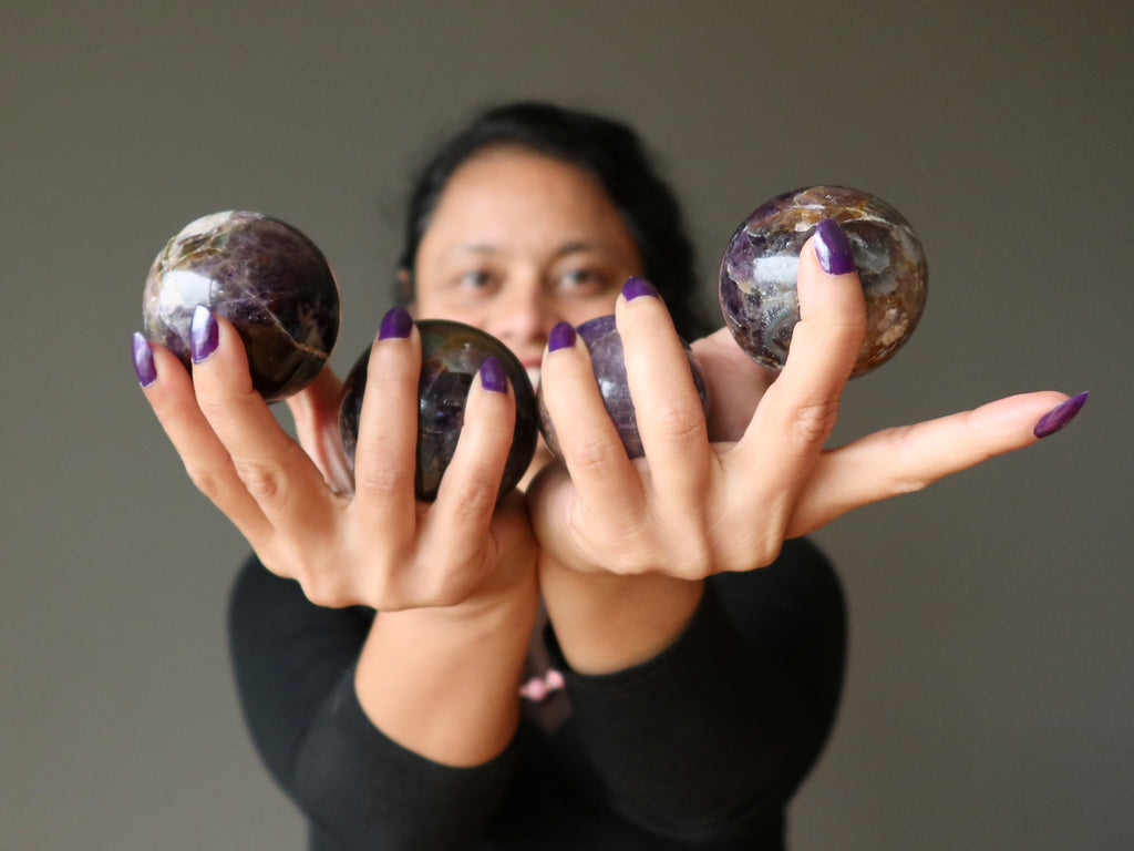 sheila of satin crystals holding 4 amethyst spheres