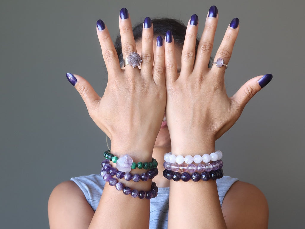 hands in front of face wearing different types of amethyst stretch bracelets and rings