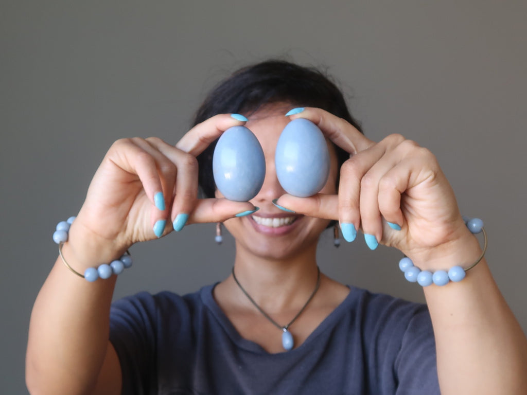 sheila of satin crystals with two blue angelite stone eggs in front of her eyes