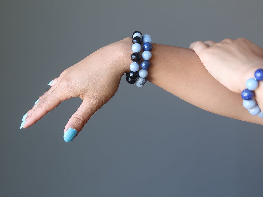 hands wearing angelite rainbow obsidian and lapis beaded stretch bracelets at satin crystals data-pin-media=