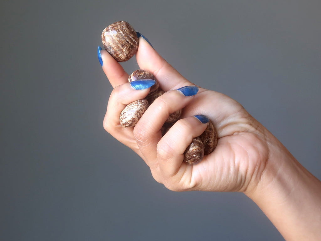hand holding up aragonite tumbled stones for crystal healing