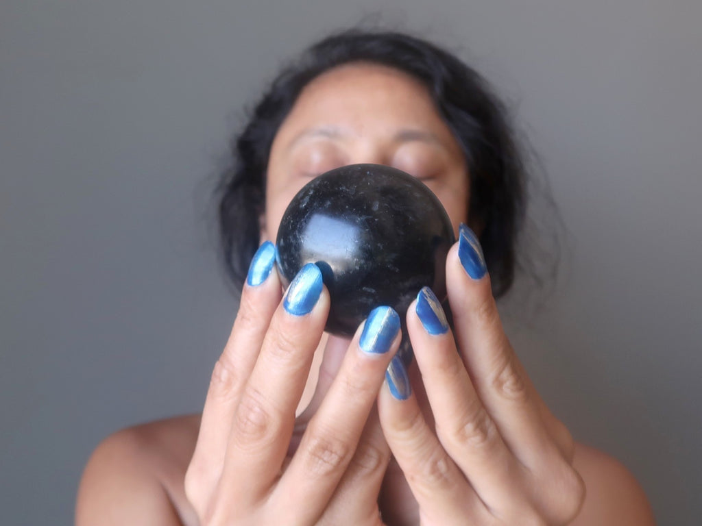 sheila of satin crystals meditating with an arfvedsonite stone sphere