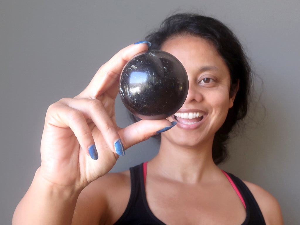 sheila of satin crystals holding up an astrophyllite stone sphere