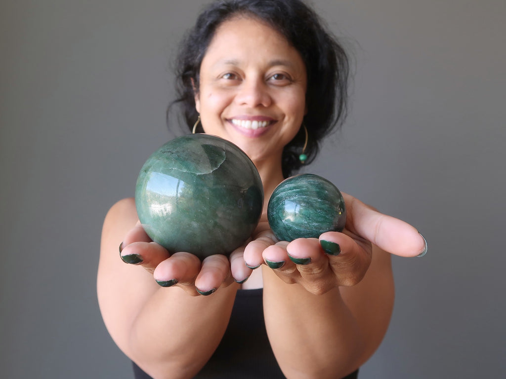 sheila of satin crystals holding two green aventurine crystal balls
