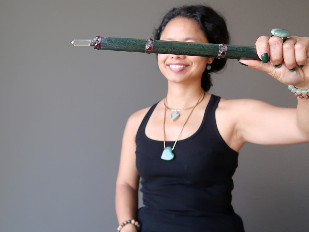 sheila of satin crystals holding a long green aventurine wand