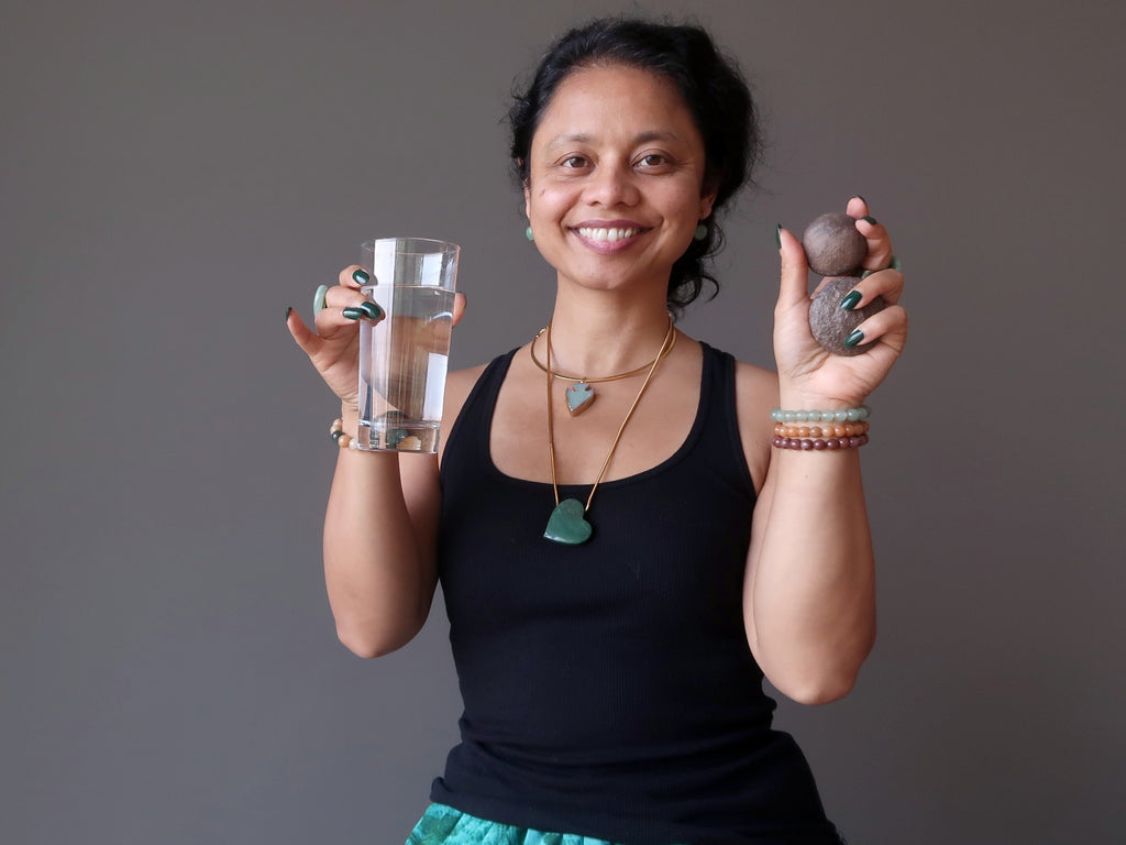 sheila of satin crystals holding moqui marble pair and a glass of water