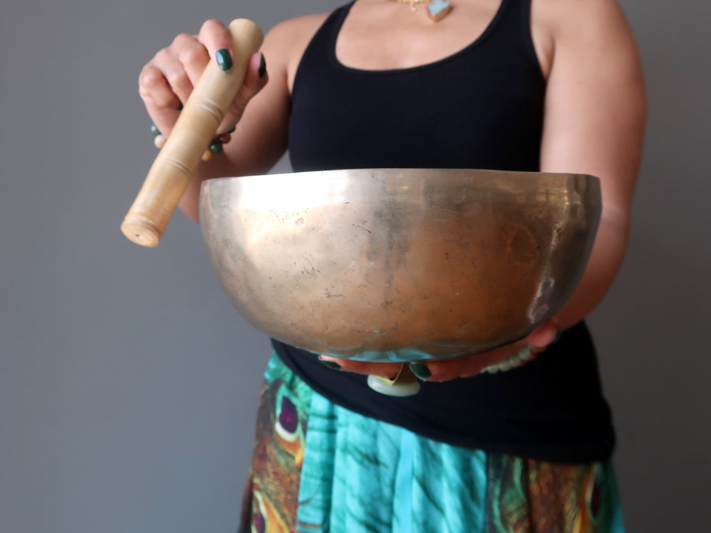 woman standing with tibetan singing bowl
